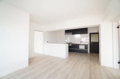 【約13帖LDK】 廊下から、新規交換された開き戸を入って すぐ右手にキッチン。目の前がリビングスペース。 キッチンは濃いめの色を用いることによって、 白で統一された室内にアクセントを与えてくれます。