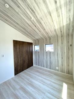 勾配天井とインパクトのあるアクセントクロスが印象的な居室です。天井が高いので、室内の大きさ以上に広々と感じて頂けます。