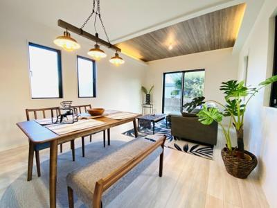 リビング部分は高天井とアクセントクロス仕様。高級感のある色合いもあって素敵な空間演出となりました。高天井サイドに雰囲気の増す間接照明もございます。なんと写真の家具もプレゼント!