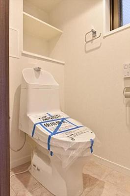 窓と収納棚付きの温水洗浄機能付きトイレです