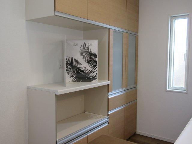 キッチンには備え付けのカップボードが標準でついています。キッチンと色合いも統一されて収納豊富な設備。