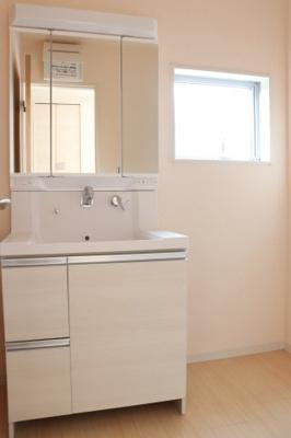 清潔感のある洗面室は小窓からの採光で明るく、風通しがいいので湿気対策も考慮されています。シンプルな洗面台は収納力だけでなくシンクも広いです。