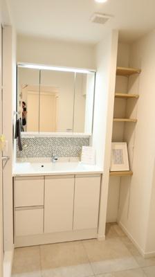バスルームへつながる側には収納棚を設置しました。入浴後のタオルや衣類、また洗剤などの洗濯用品が収納可能です。後付け収納と違い、統一感ある収納で脱衣所もスッキリ見えますね♪