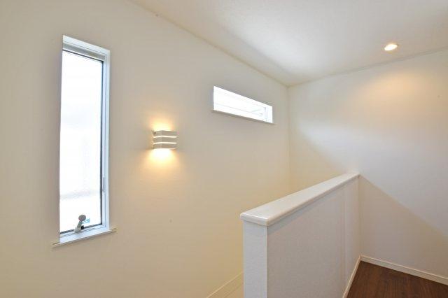 2階ホールにはダウンライトとブラケットライトに加えて、縦横に走る採光窓を設け開放感をプラス。高窓からの採光が良く見える一枚です。