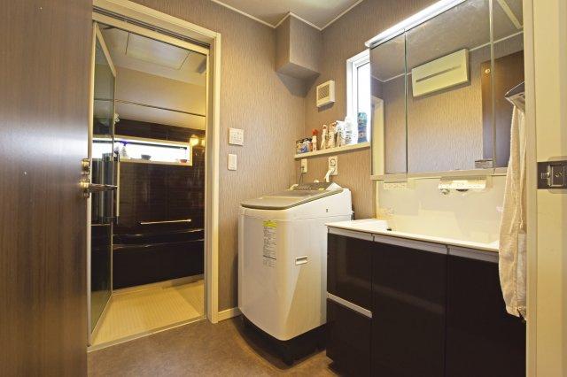 脱衣所を兼ねた洗面室は、主役となるブラックが基調の浴室に馴染むシックな配色で仕上げられています。採光窓も設け、清潔感が感じられる閉そく感の少ない空間です。