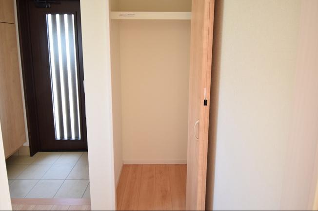玄関収納です。パイプハンガーや収納棚があるので普段よく着るアウターなども掛けられます。