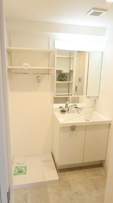 白が基調の洗面台を新規設置しております。収納豊富な三面鏡タイプです♪防水パン上にも上部に収納棚が設置されています。明るくおしゃれなパウダールームで身支度も楽々です♪
