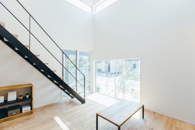 【プラン例①】 ウッドデッキに面した大きな窓が 印象的な広々としたリビング。 吹き抜けから降り注ぐ自然光が家族を明るく照らします。 高い勾配天井が開放的な空間をつくりだしています。