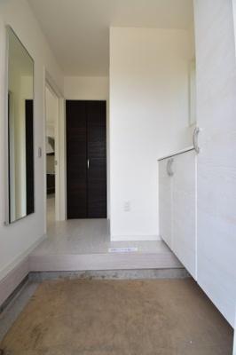 十分なスペースの玄関ホールは靴の脱ぎ履きもラクラク。壁面の姿見でお出かけ前の身だしなみチェックも。
