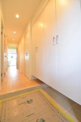 白を基調とした明るい玄関。扉を開けた瞬間、ホテルライクな空間がお出迎え。大容量シューズボックス完備。