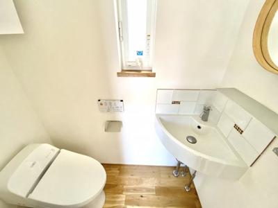 スッキリとしたデザイン性も兼ねているタンクレストイレです。手洗いスペースや鏡もついてます。窓もあるので明り取りや換気にも役立ちます。
