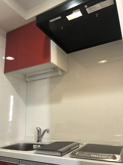 キッチンの吊戸棚もレッドで統一 フード付き換気扇もおしゃれ