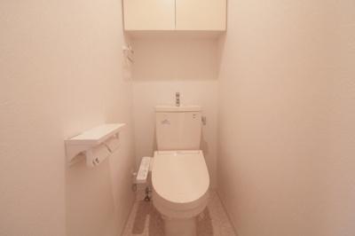 上部に吊戸棚があるウォシュレット付きトイレです
