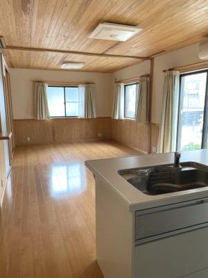 約29.24帖のリビング・ダイニング・キッチン。杉板張りの天井と腰壁がアクセントになっています。