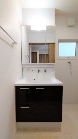 三面鏡タイプの洗面台。鏡裏や下部に大容量収納スペース。コンセント付。湯温や水量をレバー1つで調節可。