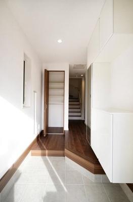 ホールに可動棚付きの収納があり、外用遊具等も収納可能です。右側には姿見付きのシューズボックスを設置。