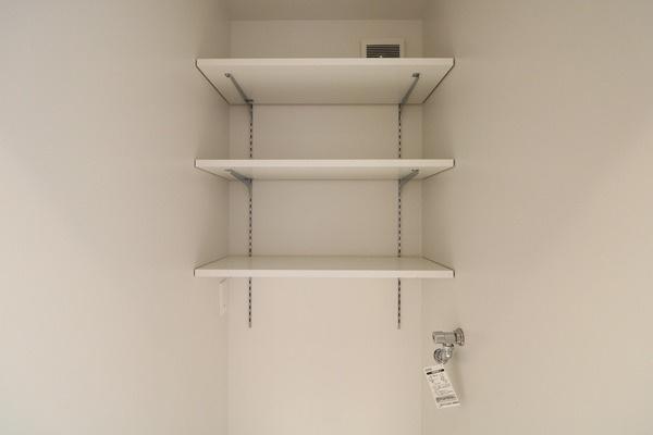 洗面所の洗濯パン上部にある高さ調整できる便利な可動棚♪