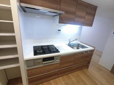 3口ガスコンロのシステムキッチンです。 横には可動棚がついており食品・備蓄品をストックできます。