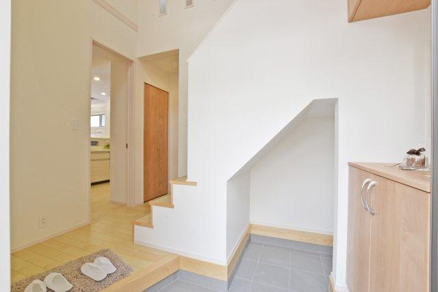 土間収納とシューズボックス付きの吹抜け玄関。階段の壁面を一部取り去った設計で開放感にこだわっています。