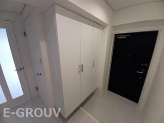 白色のタイルが貼ってある明るい玄関。廊下と玄関の段差がほぼなくフラットに使えます。