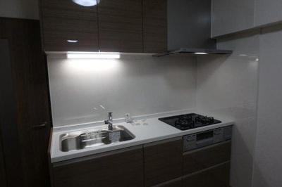 動線が短く作業しやすい、壁付けのシステムキッチンです。上下に収納スペースがあり、調理器具や食品ストックをすっきりと収納できます。