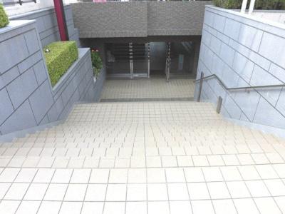 重厚なマンションの外観を見上げたら、南西側の階段を下りた先にエントランスがあります。