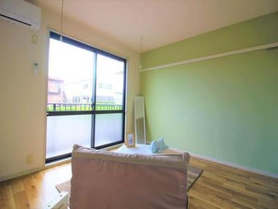 緑のアクセントクロスが映える室内