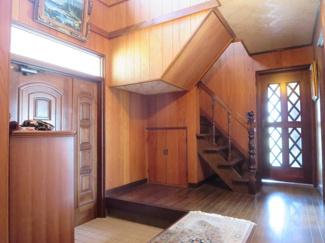 落ち着いた色で統一された木の壁と吹き抜け、木の玄関ドアの飾り窓から日差しが入る明るく広い玄関です。