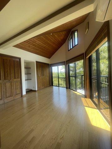 2階リビング。天井は木目のパネルがはってあります。窓からは緑が広がっています。