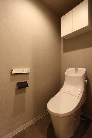 スッキリとしたデザインの温水洗浄便座搭載トイレでございます。上部吊戸棚収納もご活用下さい。