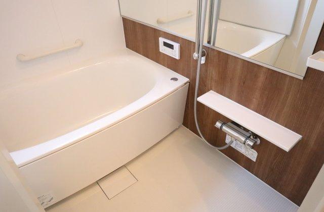 ナチュラルな色味の壁でほっと落ち着ける空間になりました。鏡を横のラインに配置することで浴室を広く見せる効果があります。