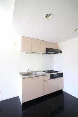 黒床と白キッチンでシンプルで引き締まった