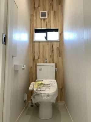 2階のトイレです。 木目調のアクセントクロスがおしゃれなトイレとなっております。 ちょっとした収納もありますよ♪温水洗浄便座完備です。