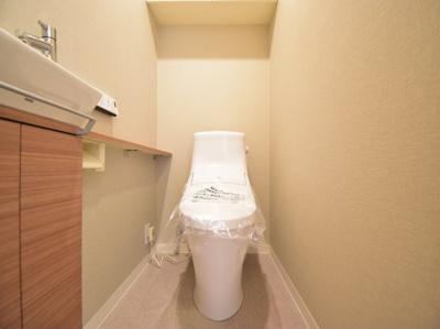 手洗い器付きの高機能トイレはシンプルでお手入れもしやすい仕様。背面収納付きで備品もスッキリ収納。