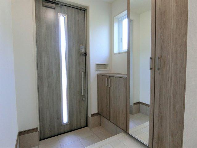 玄関ホールです。大容量のシューズロッカーにはご家族皆さまの靴を収納できます。玄関に鏡があるのは便利!