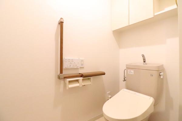 【トイレ】清潔で快適に使える、吊戸棚もあり収納ができとても便利です。また、バリアフリーに配慮し、立ち座りに安心な手摺りを設けています。