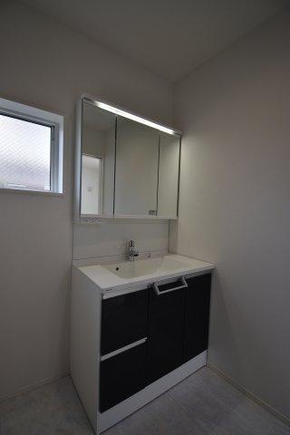 身支度に便利な三面鏡タイプの洗面化粧台。鏡の裏側は大容量の収納スペースとなっております。