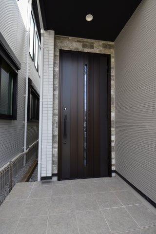 玄関は重厚感のある扉を採用。スリット状のガラスで玄関内の明るさを確保。
