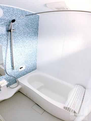 白とパステルブルーのアクセントクロス採用の明るいバスルームで、一日の疲れをリフレックス♪