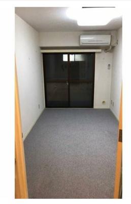洋室6帖のお部屋です。右上側にエアコン、窓はバルコニーに出ます。