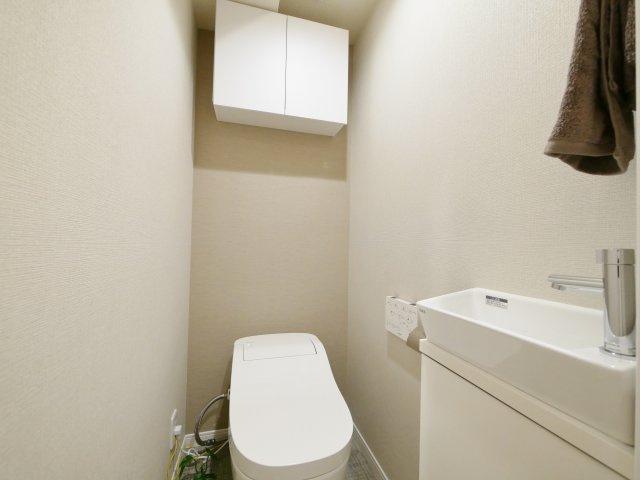トイレは場所をとらないタンクレストイレプ+手洗いカウンターがございます 備品のストックに便利な上部に吊戸棚がございます