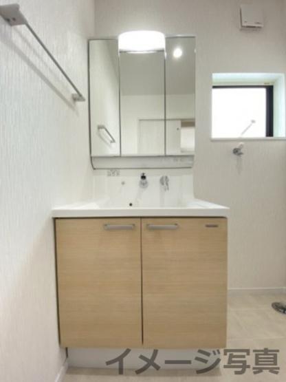 三面鏡タイプの洗面台。鏡裏や下部に大容量収納スペース。湯温や水量をレバー1つで調節可。コンセント有。