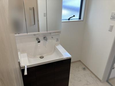 小窓からの採光で明るく、風通しがいい洗面室は湿気対策も考慮されています。シンプルな3面鏡の洗面台で収納力も充分にあり、シンクも広いです