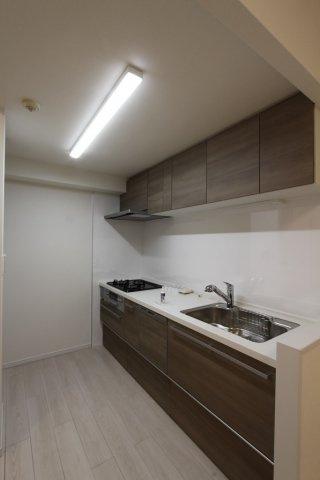 暖かみのある木目調のシステムキッチンは、嬉しい食器洗浄機付きです。  収納力もしっかりと確保した上部の戸棚も嬉しいポイントですね。