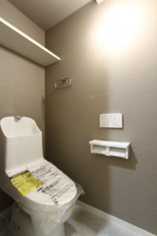 温水洗浄便座付のトイレに新規交換リフォーム済です◎ 優しいグレーのクロスがおしゃれですね。上部に造り付けの棚も役立ちます。