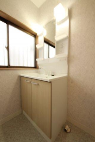 洗面化粧台は、収納もたっぷり。シャワー付きで洗髪などにも便利です。