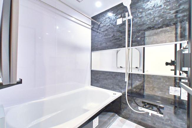 バスルームは高級感のあるダークな色調の壁で、リラックスできる空間になっています。 鏡を横のラインに配置することで浴室を広く見せる効果があります