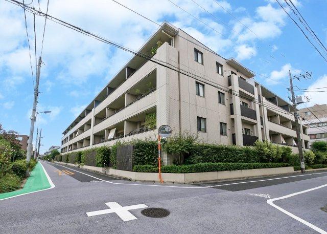 三方道路に面した地上5階建ての落ち着いた佇まいのマンション