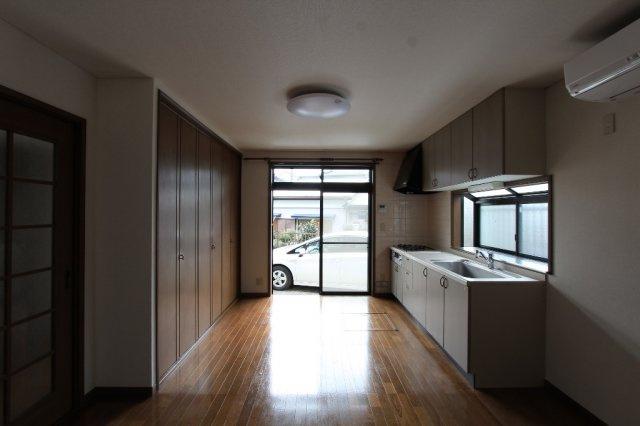 キッチンの後ろ側にはストック用品や食器など様々なものを収納できる棚が備わっているので、置場に困りませんね。フローリングは拭き掃除もスムーズに行えますよ。