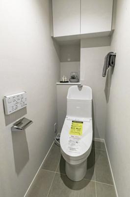 TOTO製洗浄便座付トイレを新規設置。トイレットペーパーなどの収納に便利な吊戸棚やカウンターが備え付けられています。